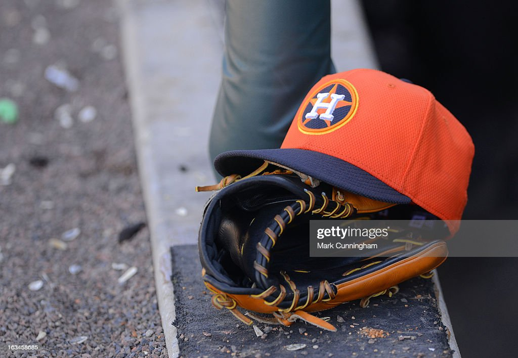 A detailed view of a Houston Astros baseball hat and glove sitting in the dugout during the spring training game against the Detroit Tigers at Joker Marchant Stadium on March 4, 2013 in Lakeland, Florida. The Tigers defeated the Astros 8-5.