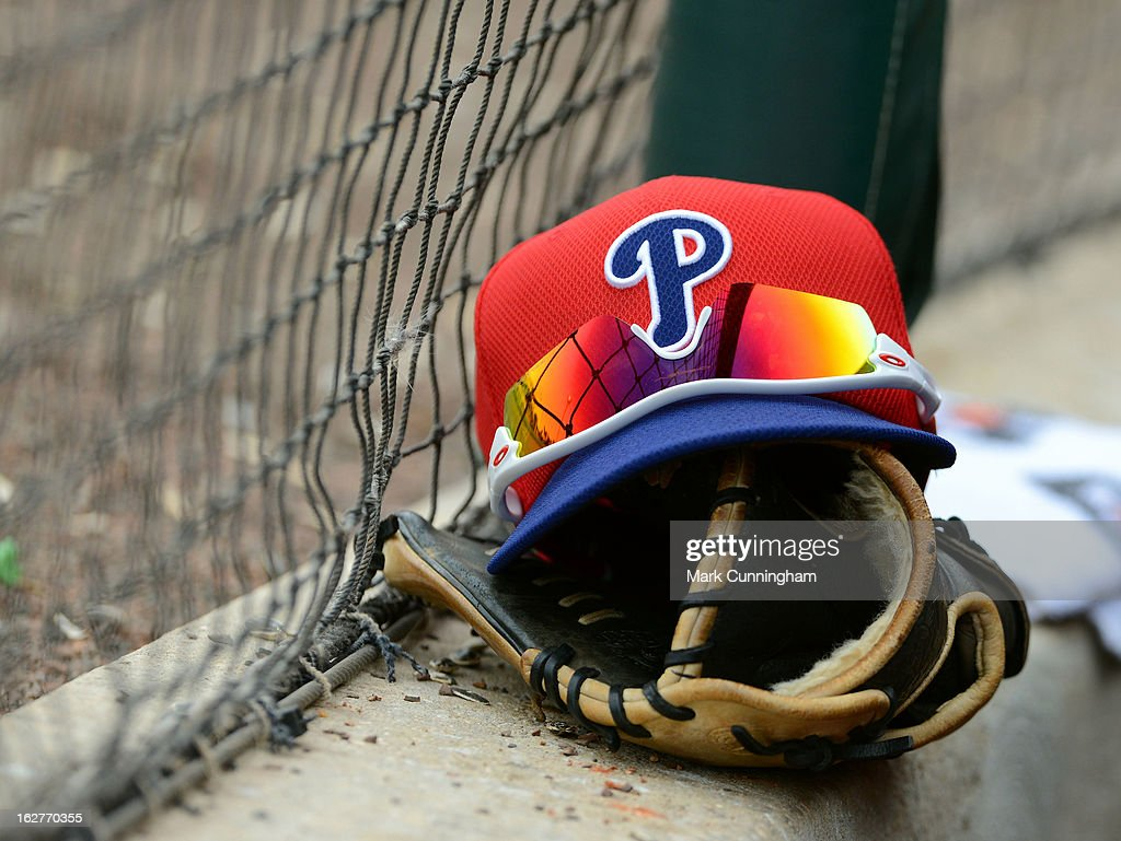 A detailed view of a Philadelphia Phillies baseball hat and glove sitting in the dugout during the spring training game against the Detroit Tigers at Joker Marchant Stadium on February 24, 2013 in Lakeland, Florida. The game ended in a 10 inning 5-5 tie.