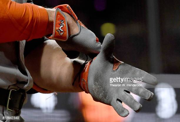 A detailed view of Giancarlo Stanton of the Miami Marlins putting on his MVP Nike batting gloves while standing in the ondeck circle against the San...