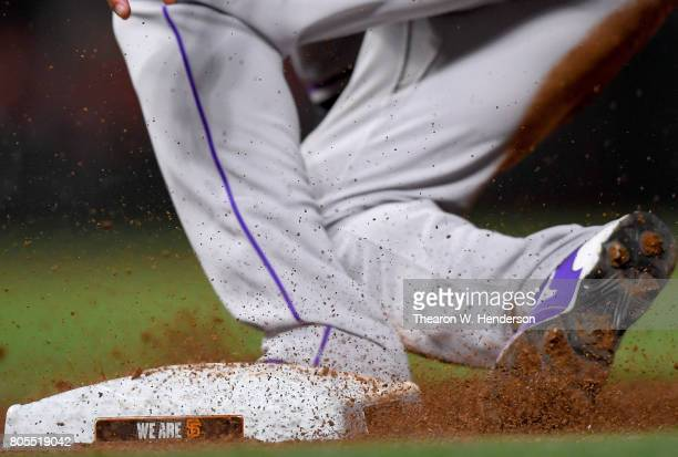 A detailed view of Ian Desmond of the Colorado Rockies wearing Mizuno baseball cleats sliding back into first base against the San Francisco Giants...