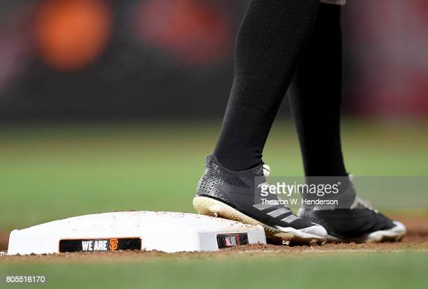 A detailed view of the Adidas baseball cleats worn by Raimel Tapia of the Colorado Rockies while standing on first base against the San Francisco...