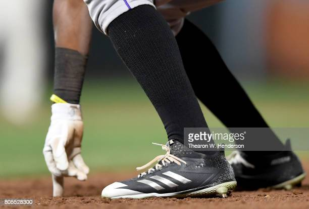 A detailed view of the Adidas baseball cleats worn by Raimel Tapia of the Colorado Rockies as he leads off first base against the San Francisco...