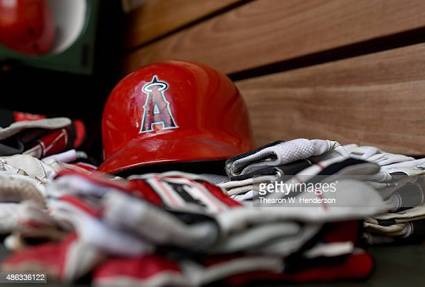 A detailed view of the batting gloves and a batting helmet belonging to the Los Angeles Angels of Anaheim sitting on the bench in the dugout prior to...