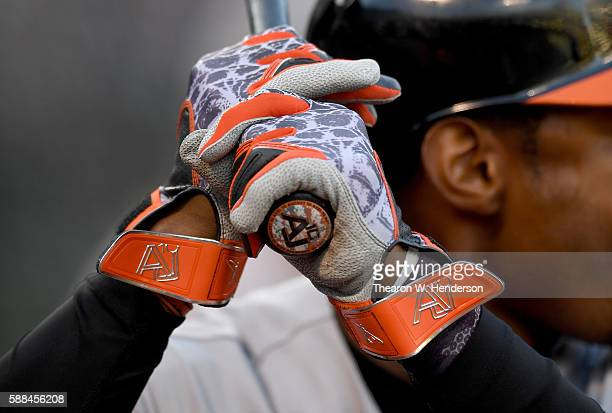 A detailed view of the Nike Swing Man batting gloves worn by Adam Jones of the Baltimore Orioles while holding his bat in the ondeck circle against...