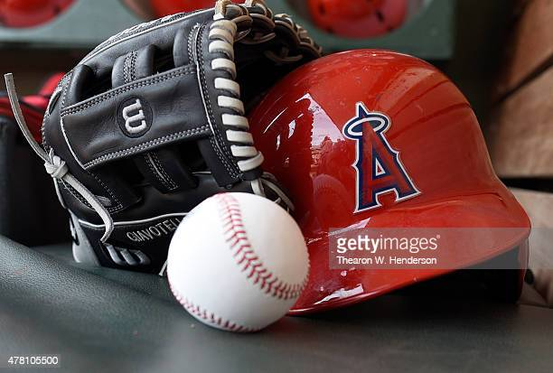 A detailed view of the Wilson baseball glove and helmet belonging to Johnny Giavotella of the Los Angeles Angels of Anaheim sitting in the dugout...