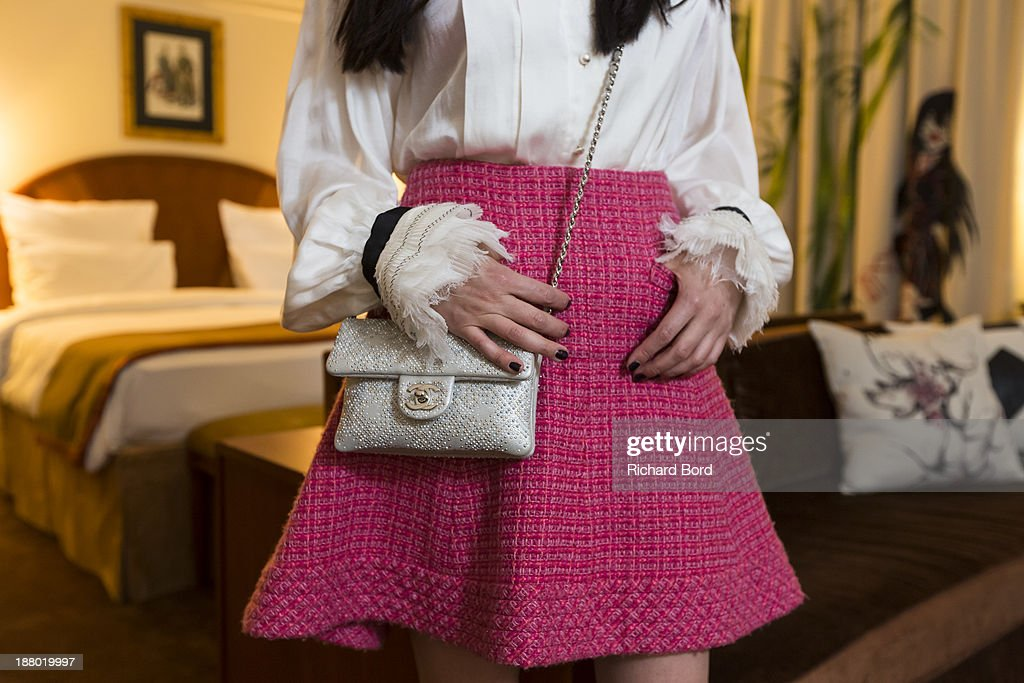 Details of artist Yi Zhou's Chanel skirt, bag and shirt as she poses in her 'Paradise Suite' she has designed at Hotel Lutetia on November 14, 2013 in Paris, France.