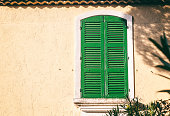 Details of French Provencal architecture, a window with green shutters