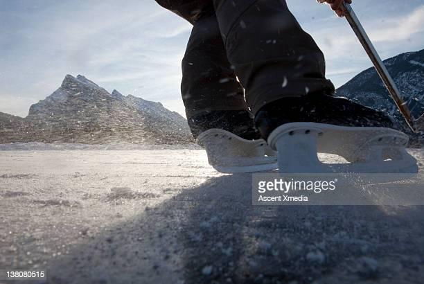 Details of skates turning on frozen pond, hockey