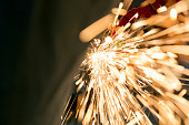 Sparks are coming out from a grinder while an employee cutting a steel tube.