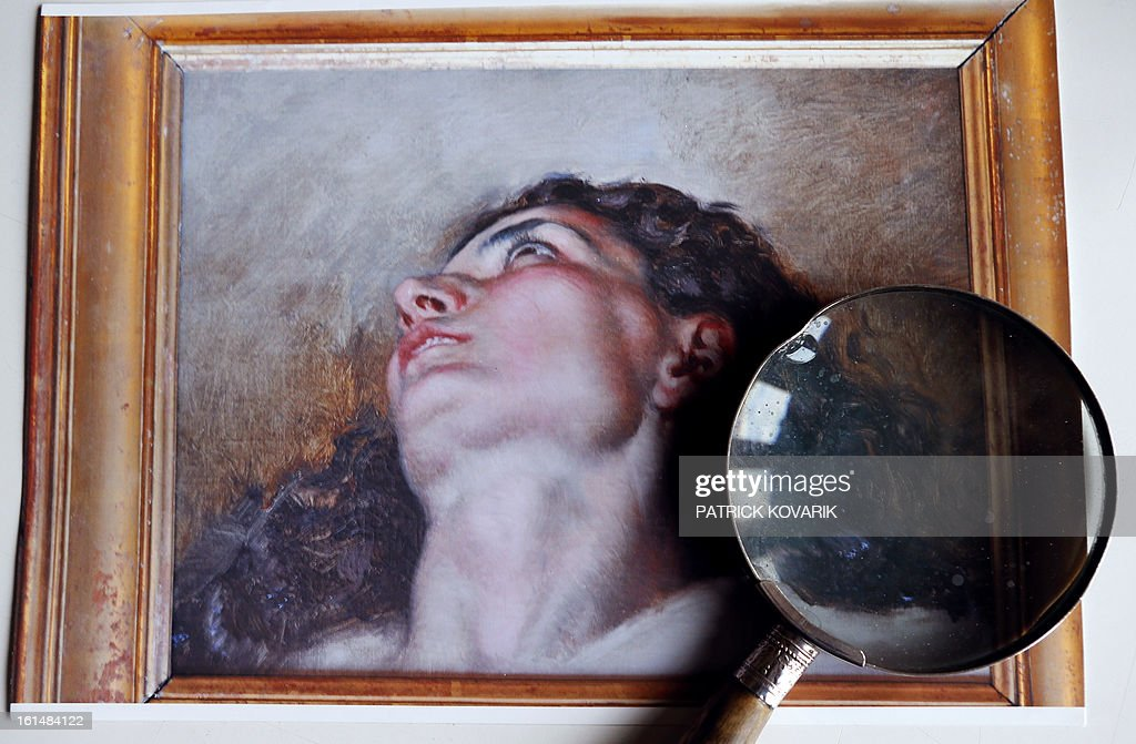 Details of the reproduction of the allegedly head of the model of the French artist Gustave Courbet's painting (1819-1877) 'L'Origine du Monde' (The Origin of the World), are seen through a magnifying glass on February 11, 2013 in Paris. Jean-Jacques Fernier, French painting expert especially of Courbet, believes he has solved the mystery of the model in a celebrated 19th century painting as a result of an art lover's 1,400 euro antique shop purchase that could turn out to be worth 40 million euros ($53.6 million), weekly Paris Match reported on February 7, 2013.
