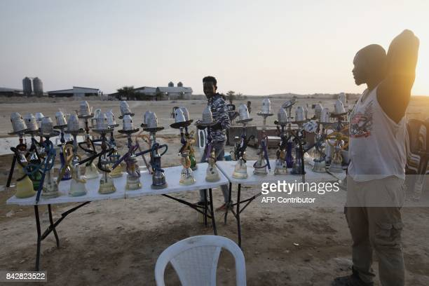 Detained African illegal immigrants prepare their waterpipes during their free time in an improvised cafe outside the Holot detention center located...