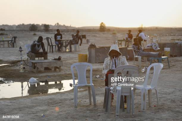 Detained African illegal immigrants smoke waterpipe during their free time in an improvised cafe outside the Holot detention center located in...