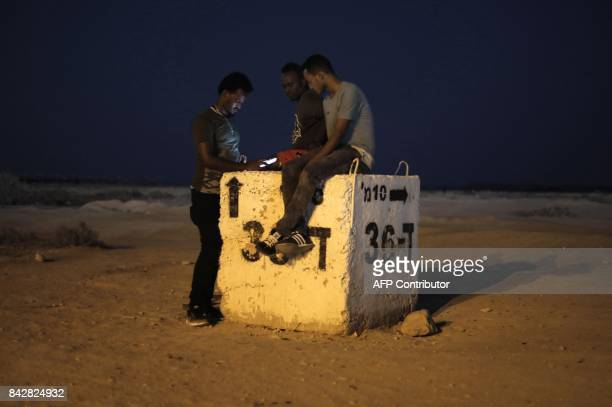 TOPSHOT Detained African illegal immigrants spend their free time outside the Holot detention center in Israel's southern Negev desert near the...