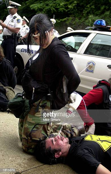 A detained demonstrator left washes out the eyes of fellow detainee David Mitchell after they were hit with tear gas June 2 2001 during a protest...