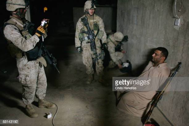 A detained man is photographed by Marines with the weapons allegedly found with him June 24 2005 near Fallujah Iraq Marines in the 3/4 launched the...