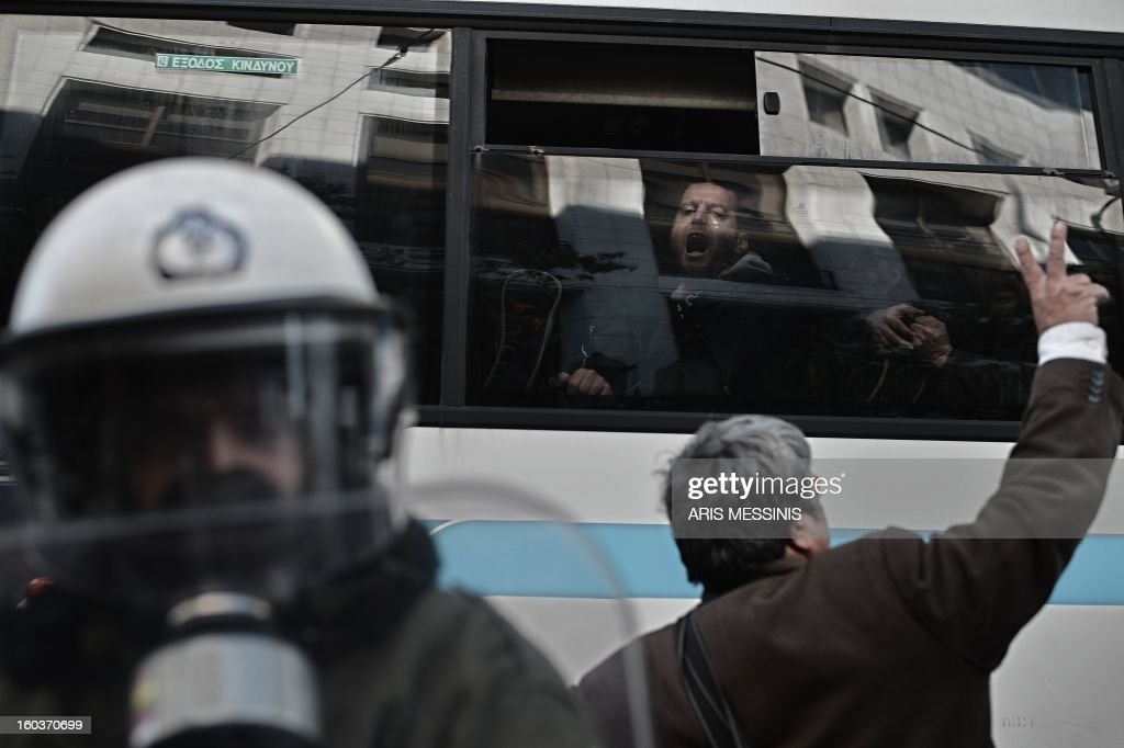 A detained protester shouts slogans outside the Labour Ministry in Athens on January 30, 2013. Police were called in on Wednesday to dislodge around 30 Communist unionists from the labour ministry in a protest against new pension cut plans. The unionists were arrested and police used tear gas outside the building to disperse a larger group of protesters demanding their release. AFP PHOTO / ARIS MESSINIS