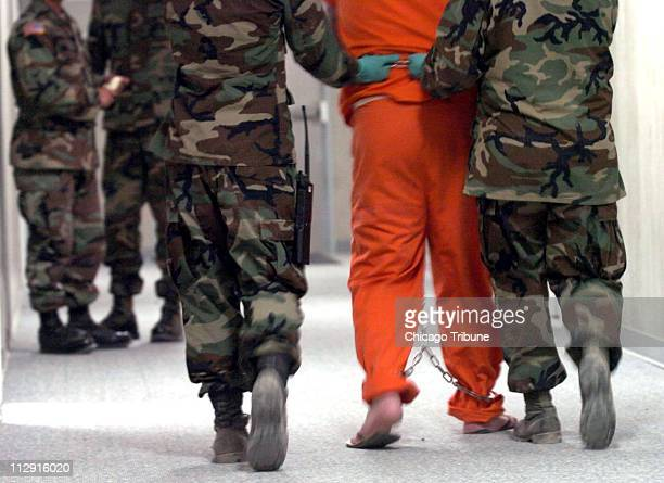 A detainee is escorted to an interrogation room at the Camp Delta detention facility at the US Marine Base in Guantanamo Bay Cuba on July 7 2004...