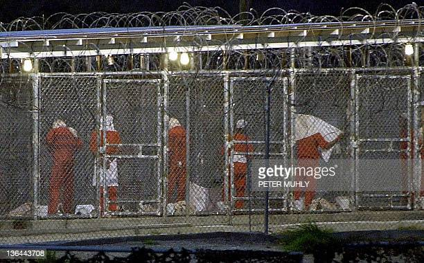 Detainees prepare themselves for the evening prayer 04 March 2002 at Camp XRay in Guantanamo Bay Cuba by facing towards Mecca Some 300 detainees from...