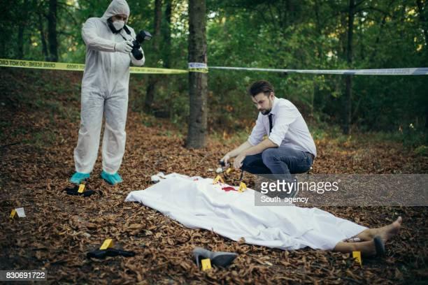 Detective and forensics on murder crime scene
