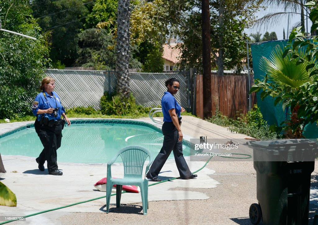 Detective Carla McCullough (R) with Rialto Police directs police technician Noretta Barker as they investigate the death of Rodney King who was found in his pool on June 17, 2012 in Rialto, California. King, whose video beating by Los Angeles police in 1991 sparked riots after the acquittal of the four officers involved, was found dead at the age of 47 from an apparent drowning in his swimming pool.