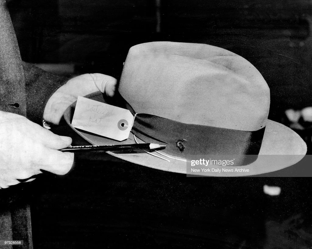 Detective indicates bullet hole in Frank Costello's hat.