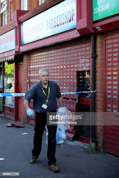 A detective removes items from a barbers shop on Princess Road Moss Side after being raided by antiterror police during the investigation of the...