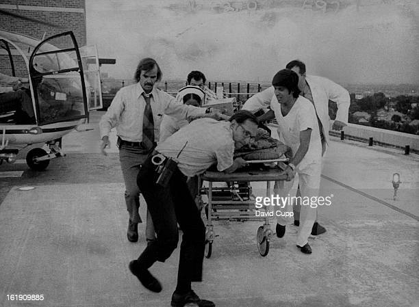 JUL 27 1973 JUL 28 1973 Detective Ron Wright Foreground helps St Anthony Hospital Emergency Crew with Patient The victim of a fall was rushed to the...