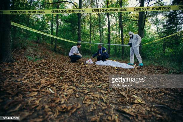 Detectives and forensics on crime scene in forest