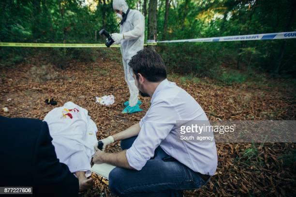 Detectives examining murder crime scene