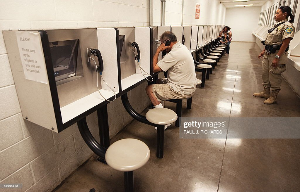 Detention Officer Rene Ansley looks on as visitors use a video phone to communicate during visiting hours with a friend or relative incarsarated...