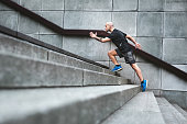 Focussed runner man jogging on stairs
