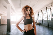 Portrait of determined african female standing in the gym. Beautiful black woman in sportswear in healthclub.