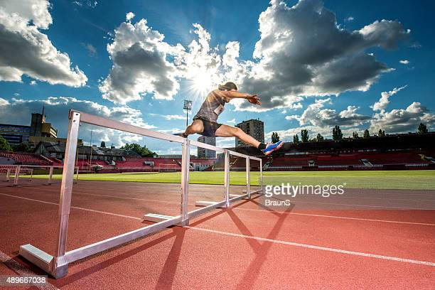 Determined athlete jumping hurdles on a sports race.