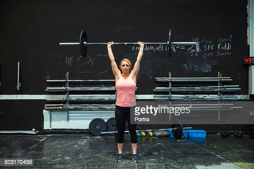 Determined athlete lifting barbell in gym