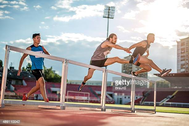 Determined athletes jumping hurdles on a sports race at stadium.