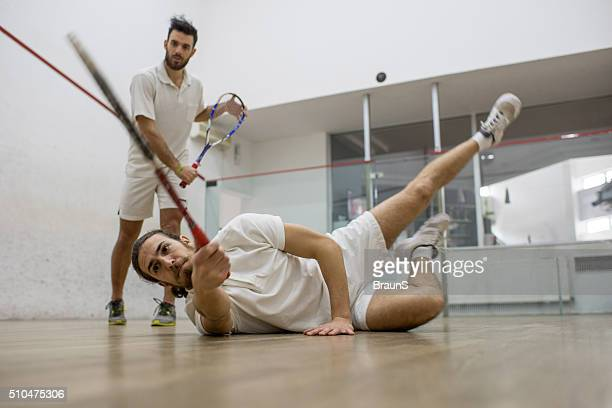 Determined athletes playing squash with great effort.