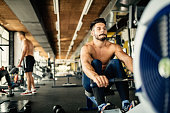Determined bodybuilder rowing in gym