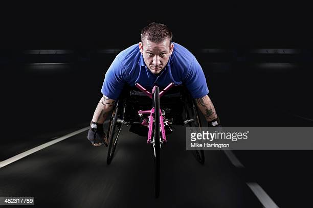 Determined disabled athlete in racing wheelchair