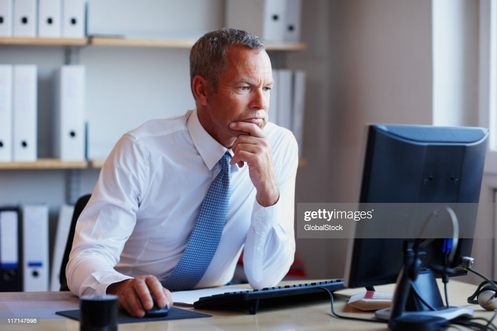 Determined executive working on project looks at computer screen : Stock Photo