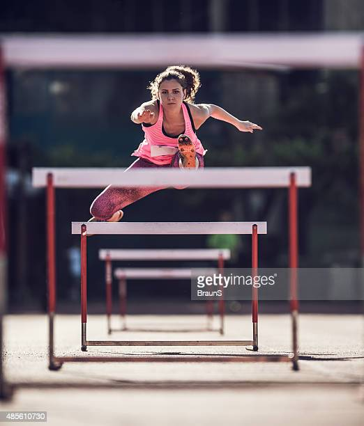 Determined female athlete jumping hurdles on a race.