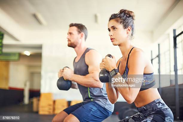 Determined female athlete with instructor exercising in health c