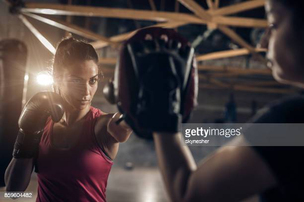 Determined female boxer having sports training with a coach.