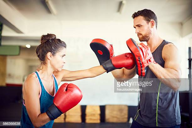 Determined female fit boxer practicing with instructor in gym