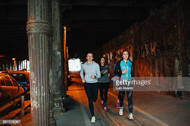 Determined female friends jogging in tunnel