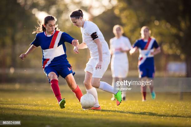 Determined female soccer players in action on a playing field.