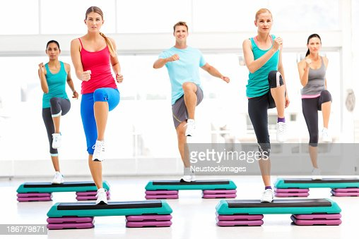 Determined Friends Doing Step Aerobics In Gym