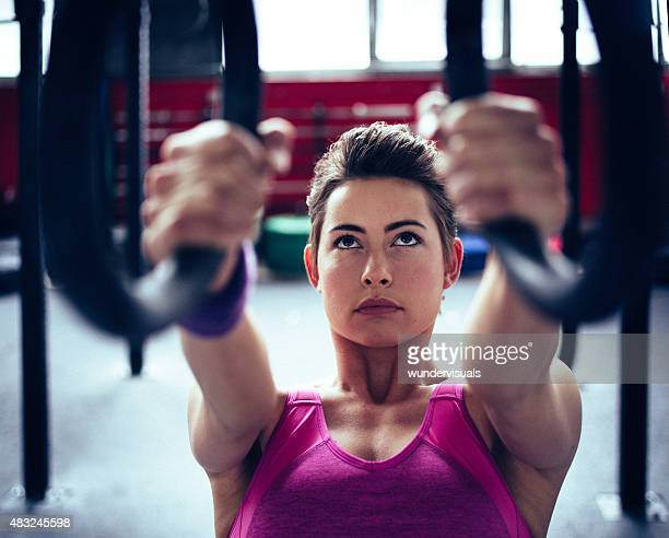 Determined girl exercising hard with gymnastic rings in a gym