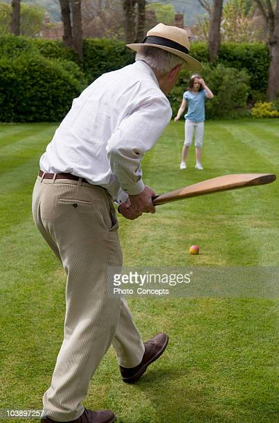 Determined grandfather bonding and playing cricket in backyard with granddaughter