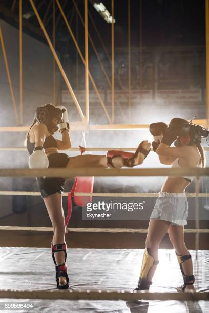 Determined kick box fighters having sports training in a ring.
