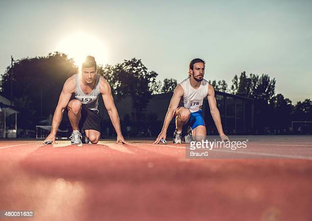 Determined male athletes ready to start a relay race.